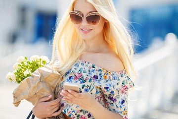 Portrait of a young blonde with a mobile phone
