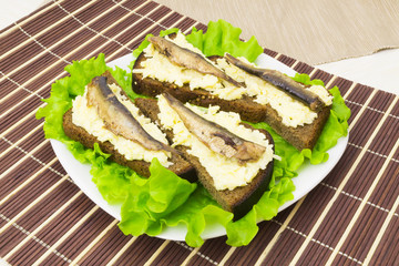 Sprats on bread with cheese and garlic