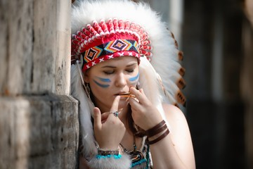 Young woman in war bonnet of American Indian plays on jew`s-harp