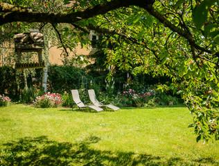 Deckchair on the lawn under cherry tree.