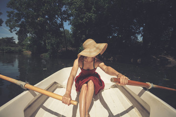 Woman rowing a boat in summer