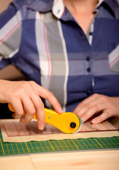 Close-up female hands cutting fabric with rotating cutter