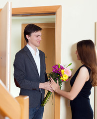 Man giving bunch of flowers to his woman