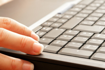 Woman hand typing on the notebook