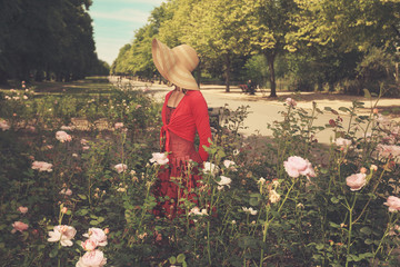 Young woman standing amongst roses in park