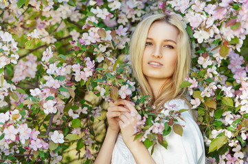 Portrait of gorgeous spring girl in blooming apple tree