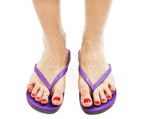 Female legs with flip-flops on white background