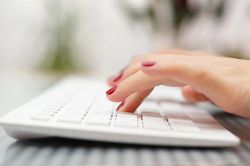 female fingers typing on white keyboard