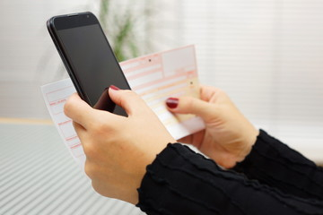 Woman is paying bill on mobile smart phone