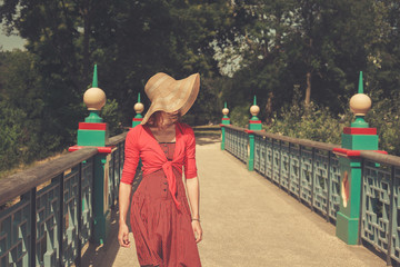 Woman wearing a red dress on bridge in a park