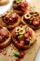 Crostini with  tomato salsa, olives, capers and herbs