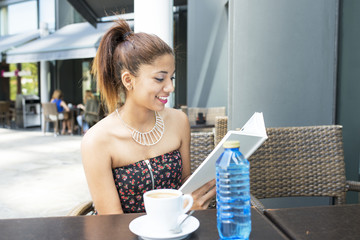 Smiling woman reads book in the terrace restaurant.