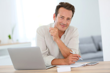 Smiling attractive man working from home