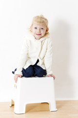 kneeling little girl wearing white sweater