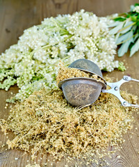 Herbal tea of meadowsweet in strainer on board