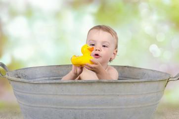 Kind mit Badeente in der Wanne