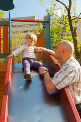 Little girl with dad on  playground.