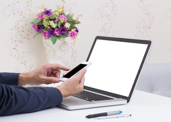Business man hands using mobile phone with blank screen laptop c