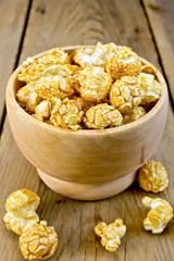 Popcorn caramel in wooden bowl on board