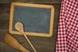 Leere Schiefertafel mit Kochlöffeln und rot karierten Tischtuch