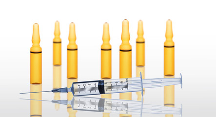 Syringe and yellow medical ampules isolated on white