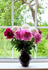 vase with colorful peonies on window-sill