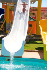 Pretty blonde woman riding down a waterslide