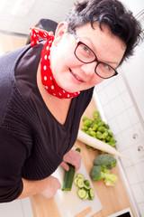 Übergewichtige Frau beim Gemüse schneiden