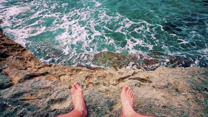 feet on a rock and sea