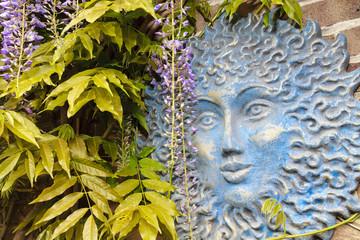 Blue sun face in garden