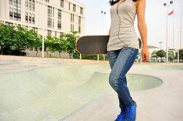 skateboarder walking at modern skatepark