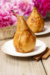 Pear with caramel, beautiful pink peonies in the background