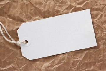 Blank white luggage tag on crumpled parcel paper