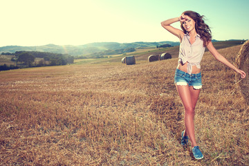 Girl walking on the field in the countryside