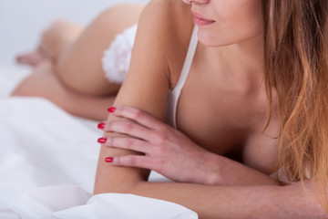 Woman with red nails is in white lingerie