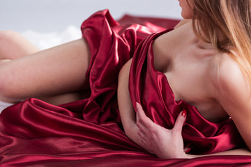 Naked woman lying covered with red material