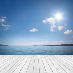 Landschaft mit Holz und See / Meer im Hintergrund