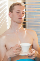 Shirtless man enjoying sunny day sitting near the window