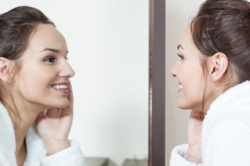 Woman watching in mirror her skin condition after treatments