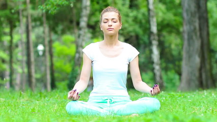 Young woman meditating in park.