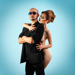 Serious strong man with hot naked woman in studio