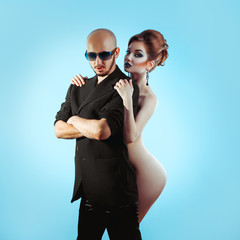 Fashion man with sexual naked woman in studio