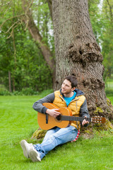 Man sitting on grass and playing guitar