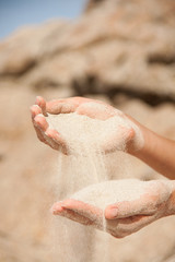 sand flows through the female hands