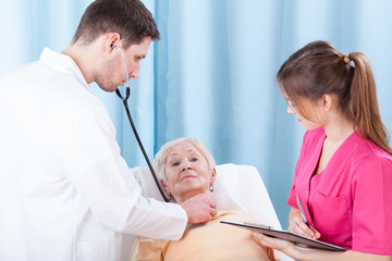 Young doctor examining elderly lady