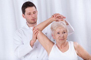 Physiotherapist rehabilitating elderly woman