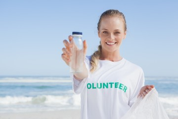 Blonde smiling volunteer picking up trash on the beach