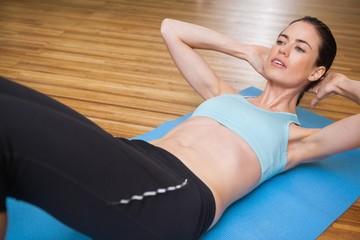 Fit brunette doing sit ups in fitness studio