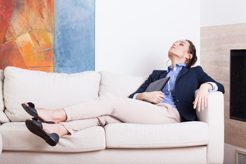 Businesswoman resting on sofa after work