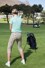 Female concentrating golfer teeing off